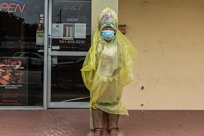 The cigar store indian statue in front of the Cigar Factory on Belvedere Road in West Palm Beach is dressed for the wet weather and wears a mask to fight the spread of the coronavirus, Wednesday, October 21, 2020. (JOSEPH FORZANO / THE PALM BEACH POST)