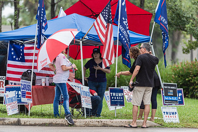 Supporters of President Donald J. Trump talk while surrounded by pro Trump flags and signs near the West Boca Branch Library in Boca Raton, Friday, October 23, 2020. Statewide early voting started in Florida on Monday. (JOSEPH FORZANO / THE PALM BEACH POST)