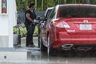 A woman gases up her car out of the rain, under the canopy of the Shell gas station at the 4 Points Market and Eatery on State Road 7 in Boynton Beach, Friday, October 23, 2020. (JOSEPH FORZANO / THE PALM BEACH POST)