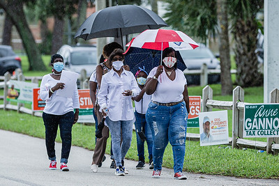 A group of friends walks under umbrellas during a light rain to the polling place at the Wells Recreation Center in Riviera Beach, Sunday, October 25, 2020. The group Black Men Stand Up organized an event to ensure at least 500 black men voted on Sunday. (JOSEPH FORZANO / THE PALM BEACH POST)