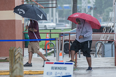 Two men walk under umbrellas during an afternoon shower to the polling place at the Wells Recreation Center in Riviera Beach, Sunday, October 25, 2020. The group Black Men Stand Up organized an event to ensure at least 500 black men voted on Sunday. (JOSEPH FORZANO / THE PALM BEACH POST)