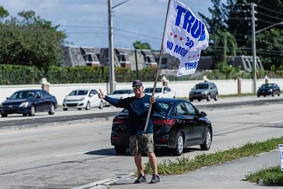 A supporter of President Donald J. Trump waves a Trump flag outside the Lantana Road Branch Library in Lake Worth on Election Day, November 3, 2020. (JOSEPH FORZANO / THE PALM BEACH POST)