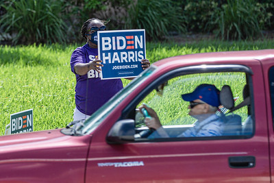 A supporter of Vice President Joe Biden waves a Biden/Harris sign outside the Lantana Road Branch Library in Lake Worth on Election Day, November 3, 2020. (JOSEPH FORZANO / THE PALM BEACH POST)