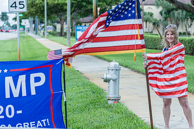 Rose Marie Heath of Boca Raton is wrapped in an American flag as she cheers for President Donald Trump in front of Ascension Catholic Church in Boca Raton, on Election Day, Tuesday, November 3, 2020. (JOSEPH FORZANO / THE PALM BEACH POST)