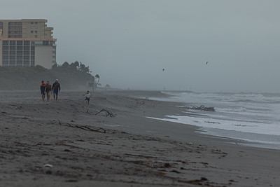 A family walks on Jupiter Beach in the aftermath of Tropical Storm Eta passing South Florida, Monday, November 9, 2020. (JOSEPH FORZANO / THE PALM BEACH POST)