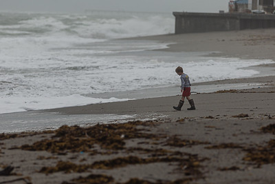 A boy plays at the edge of the rough surf on Jupiter Beach in Jupiter, which was churned up by the passing of Tropical Storm Eta, Monday, November 9, 2020. (JOSEPH FORZANO / THE PALM BEACH POST)