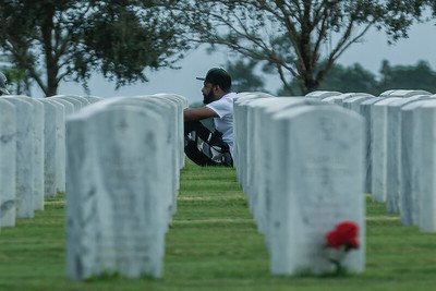 A man sits quietly surrounded by headstones of fallen veterans at the South Florida National Cemetery in Lake Worth on Veteran's Day, Wednesday, November 11, 2020. (JOSEPH FORZANO / THE PALM BEACH POST)