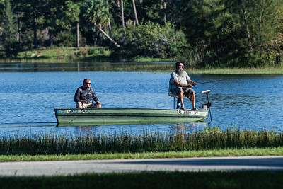 Two men fish from a boat in the lake at Okeeheelee Park in West Palm Beach, Friday, November 13, 2020. Largemouth bass, channel catfish, bluegills,  redear sunfish, Mayan cichlid and spotted tilapia can be found in the lakes at Okeeheelee. (JOSEPH FORZANO / THE PALM BEACH POST)