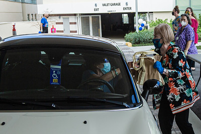 Beth Foster from the Kravis Center finance department takes a donated bag of non-perishable food from a volunteer at the Kravis Center for the Performing Arts Drive-Through Volunteer Salute, in West Palm Beach, Tuesday, November 17, 2020. The event was hosted to allow staff to thank the dedicated volunteers who devote their time and effort  at the Kravis Center throughout the year. (JOSEPH FORZANO / THE PALM BEACH POST)