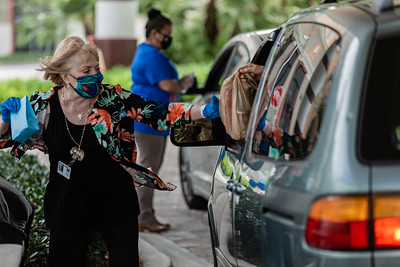 Beth Foster from the Kravis Center finance department takes a donated bag of non-perishable food from a volunteer before handing them a gift bag at the Kravis Center for the Performing Arts Drive-Through Volunteer Salute, in West Palm Beach, Tuesday, November 17, 2020. The event was hosted to allow staff to thank the dedicated volunteers who devote their time and effort  at the Kravis Center throughout the year. (JOSEPH FORZANO / THE PALM BEACH POST)