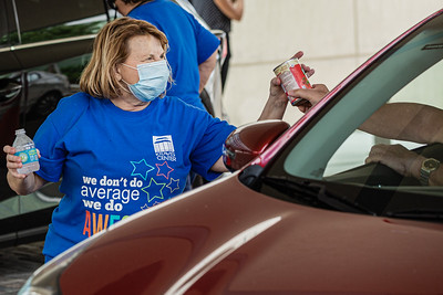Karole Cooney, Event Manager at the Kravis Center, receives a can of non-perishable food from a volunteer at the Kravis Center for the Performing Arts Drive-Through Volunteer Salute, in West Palm Beach, Tuesday, November 17, 2020. The event was hosted to allow staff to thank the dedicated volunteers who devote their time and effort  at the Kravis Center throughout the year. (JOSEPH FORZANO / THE PALM BEACH POST)