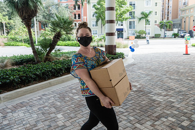 Kelsey Cornnell, Administrative Assistant at the Kravis Center, carries two boxes of donated non-perishable food from a volunteer at the Kravis Center for the Performing Arts Drive-Through Volunteer Salute, in West Palm Beach, Tuesday, November 17, 2020. The event was hosted to allow staff to thank the dedicated volunteers who devote their time and effort  at the Kravis Center throughout the year. (JOSEPH FORZANO / THE PALM BEACH POST)