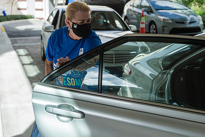 Janet Poland, Event Manager at the Kravis Center, get a bag of donated non-perishable food from the back seat of a volunteers car at the Kravis Center for the Performing Arts Drive-Through Volunteer Salute, in West Palm Beach, Tuesday, November 17, 2020. The event was hosted to allow staff to thank the dedicated volunteers who devote their time and effort  at the Kravis Center throughout the year. (JOSEPH FORZANO / THE PALM BEACH POST)