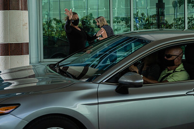 Bonnie Cillo from the Kravis Center IT departments waves at  volunteers as they drive through the valet area during the Kravis Center for the Performing Arts Drive-Through Volunteer Salute, in West Palm Beach, Tuesday, November 17, 2020. The event was hosted to allow staff to thank the dedicated volunteers who devote their time and effort  at the Kravis Center throughout the year. (JOSEPH FORZANO / THE PALM BEACH POST)