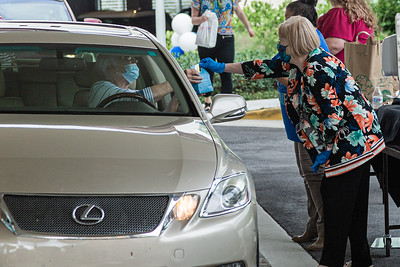 Beth Foster from the Kravis finance department hands a volunteer a gift bag at the Kravis Center for the Performing Arts Drive-Through Volunteer Salute, in West Palm Beach, Tuesday, November 17, 2020. The event was hosted to allow staff to thank the dedicated volunteers who devote their time and effort  at the Kravis Center throughout the year. (JOSEPH FORZANO / THE PALM BEACH POST)