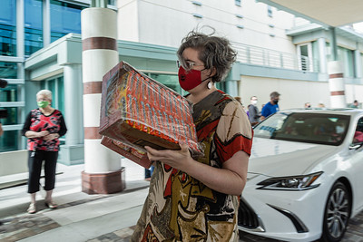 Talya Lerman, Development Manager at the Kravis Center carries two boxes of Ramen noodles that were donated at the Kravis Center for the Performing Arts Drive-Through Volunteer Salute, in West Palm Beach, Tuesday, November 17, 2020. The event was hosted to allow staff to thank the dedicated volunteers who devote their time and effort  at the Kravis Center throughout the year. (JOSEPH FORZANO / THE PALM BEACH POST)