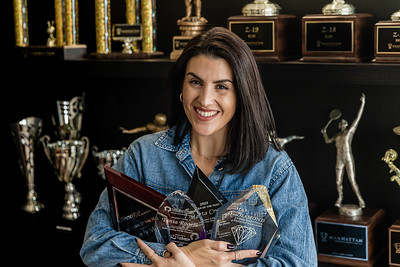Caressa Gonzalez, co-owner of Manhattan Trophies in Lake Worth Beach, holds a variety of plaques and glass trophies, on Friday, November 20, 2020. (JOSEPH FORZANO / THE PALM BEACH POST)
