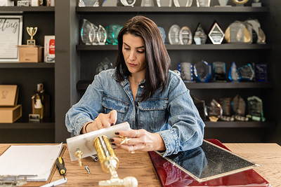 Caressa Gonzalez, co-owner of Manhattan Trophies in Lake Worth Beach, assembles a trophy in the store on Friday, November 20, 2020. (JOSEPH FORZANO / THE PALM BEACH POST)