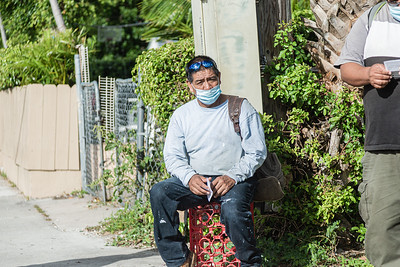 Guillermo (no last name given), waits on the corner of Broadway Avenue and 44th Street in West Palm Beach for a company who needs labor help, Friday, November 20, 2020. Guillermo, 59, originally from Guatemala, lives in West Palm Beach and has been a day laborer for 2 years. He is an experienced painter and landscaper.  (JOSEPH FORZANO / THE PALM BEACH POST)