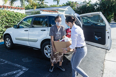 Maricela Torres (right), President of the Board and Interim Director of the Esperanza Center in West Palm Beach, helps Amelia Hoyos carry a box of non-perishable groceries that Hoyos brought to donate to the Esperanza Center, Friday, November, 20, 2020. (JOSEPH FORZANO / THE PALM BEACH POST)