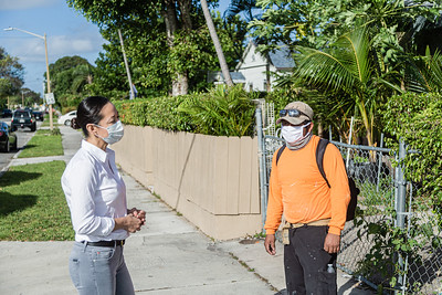 Maricela Torres (right) from the Esperanza Center speaks with Duglas (no last name given) a day laborer, on the corner of Broadway Avenue and 44th Street in West Palm Beach, Friday, November 20, 2020. Torres is the President of the Board and Interim Director of the Esperanza Center in West Palm Beach. While they distribute food on some days their main business is helping connect day laborers with jobs in a safe manner. (JOSEPH FORZANO / THE PALM BEACH POST)