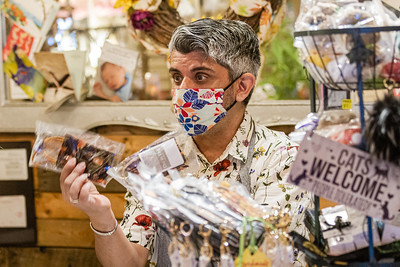 Will Davis, owner of DAY BY DAY Shoppe in Northwood Village holding up one of the handmade masks he sold at the start of the COVID-19 pandemic. A Northwood Village resident, Davis, had to close his shop from March until June 2 because of the coronavirus. Davis has owned his shop for nearly five years and is also the President of the Northwood Village Merchant Association. (JOSEPH FORZANO / THE PALM BEACH POST)