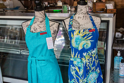 Carol Gallant, owner of Bistro Bistro in Northwood Village is starting a new line of hand crafted kitchen wear and other accessories, called La Coquine. These aprons are on display at Bistro Bistro, Saturday, November 28, 2020. (JOSEPH FORZANO / THE PALM BEACH POST)