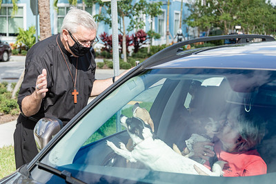 Bishop Barry Becchio from the Church of the Holy Spirit in Jensen Beach, blesses a car-full of chihuahuas at Furry Friends Adoption Clinic & Ranch in Jupiter, Sunday, November 29, 2020. Furry Friends hosted a drive by Blessing of the Animals, where all animals were blessed with prayer and holy water. (JOSEPH FORZANO / THE PALM BEACH POST)