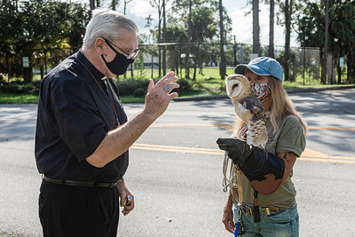 Bishop Barry Becchio from the Church of the Holy Spirit in Jensen Beach, blesses Jacques, a barn owl, held by Sunny Quinn, a docent from Busch Wildlife Sanctuary at Furry Friends Adoption Clinic & Ranch in Jupiter, Sunday, November 29, 2020. Furry Friends hosted a drive by Blessing of the Animals, where all animals were blessed with prayer and holy water. (JOSEPH FORZANO / THE PALM BEACH POST)