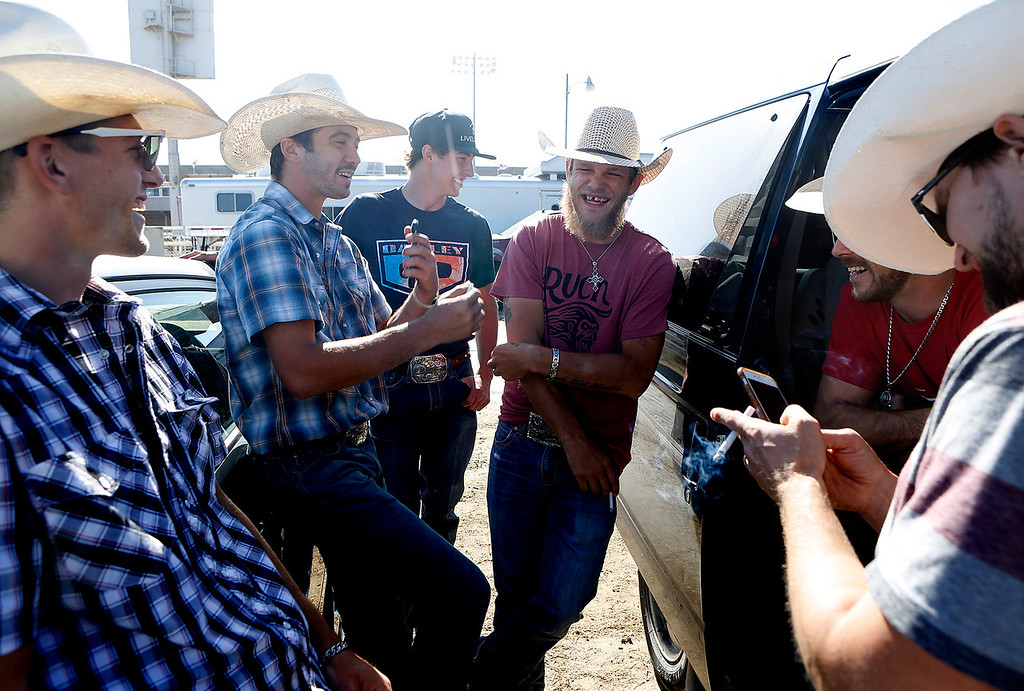 . Brandon Davis, second from left, 27, speaks with other professional bull riders prior to competing in the PBR event at the Salinas Rodeo grounds on Wednesday July 19, 2017. Davis was telling his friends about finding out their was hardly any oil in his high mileage van on the drive to Salinas. (David Royal/Herald Correspondent)
