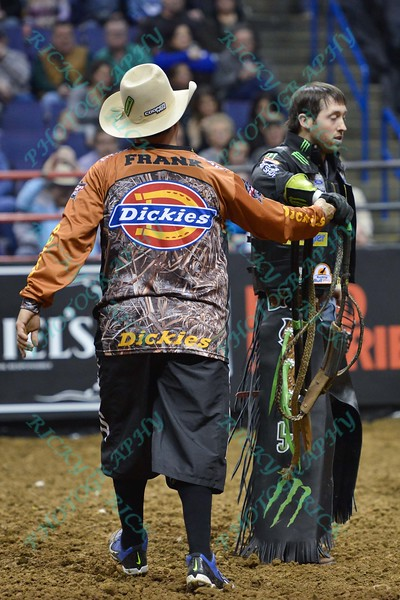 Bullfighter FRANK NEWSOM (orange) gives Rider L.J. JENKINS his ropes during the first round at the Professional Bull Riders Built Ford Tough Series, Bass Pro Chute Out presented by Cooper Tires at the Scottrade Center in St. Louis, Missouri