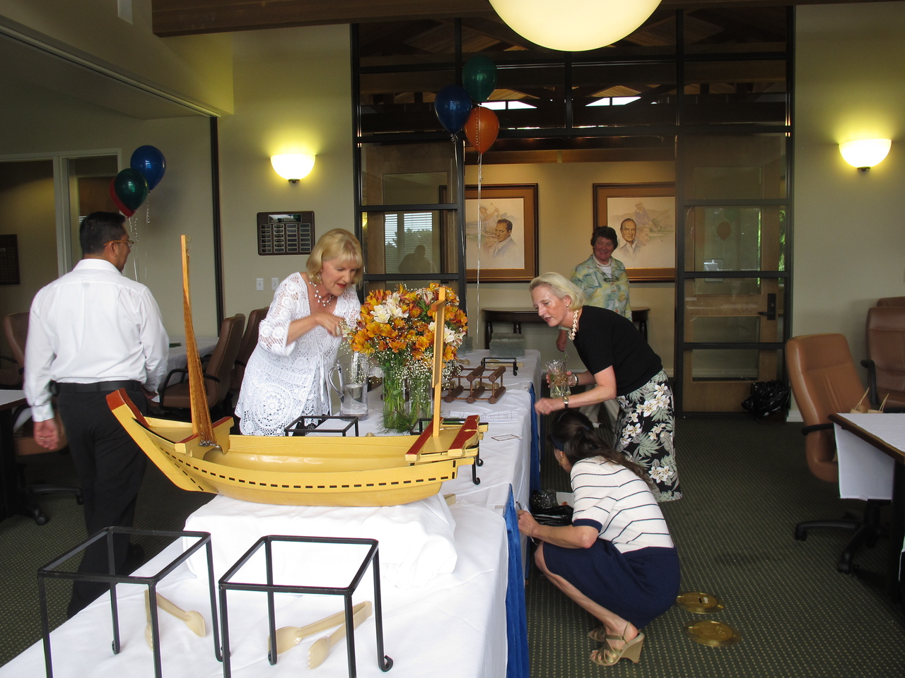 Jeannie Young and Kim Caneer put the finishing touches on the flowers while Marie-France looks on in approval.