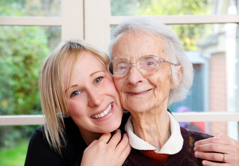 a young happy woman huggs an older happy elderly women
