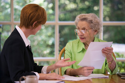 Mature woman talking to financial planner at home