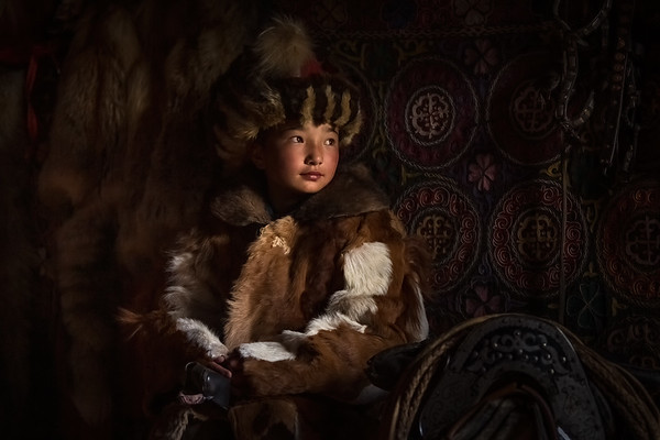 Sitting portrait of young Kazakh girl wearing traditional winter coat and hat next to a saddle and bridles, Altai Mountains, Mongolia