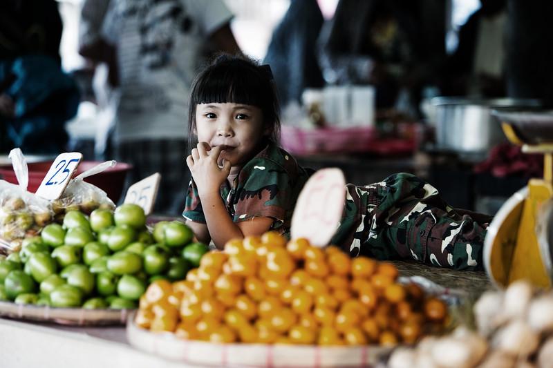 A young market trader near Chiang Rai, Thailand