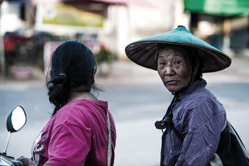 An old man leaving a food market near Chiang Rai, Thailand