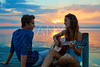 Couple playing guitar in sunset pier at dusk beach