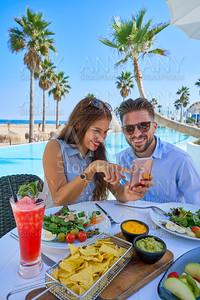 Young couple with smartphone in pool restaurant