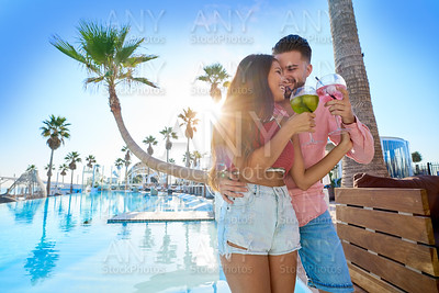Young couple drinking cocktail in pool resort