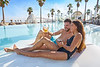 Young couple on pool hammock at beach resort