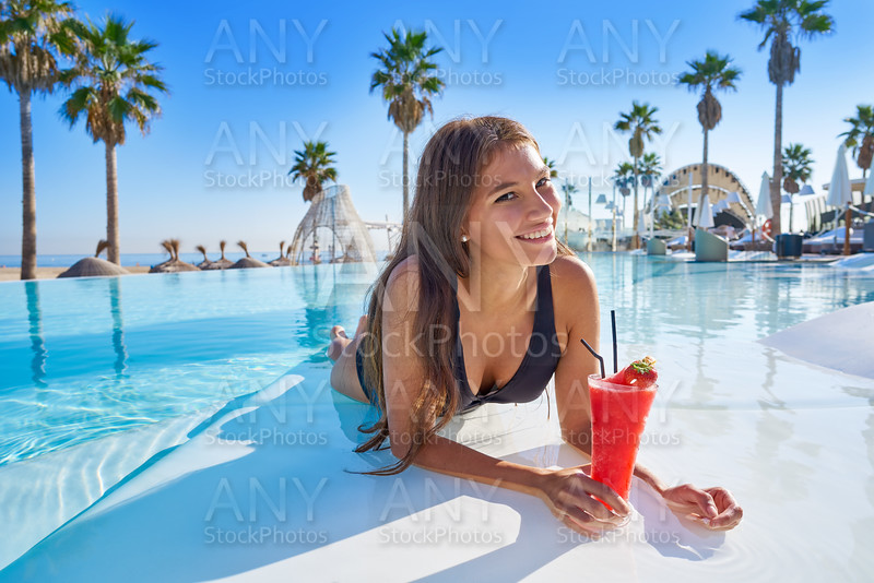 beautiful woman on infinity pool with cocktail