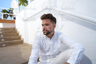 young beard man in a white starway