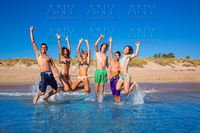 Happy excited teen boys and girls beach jumping