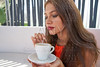 Young latin woman having coffee in lounge bar