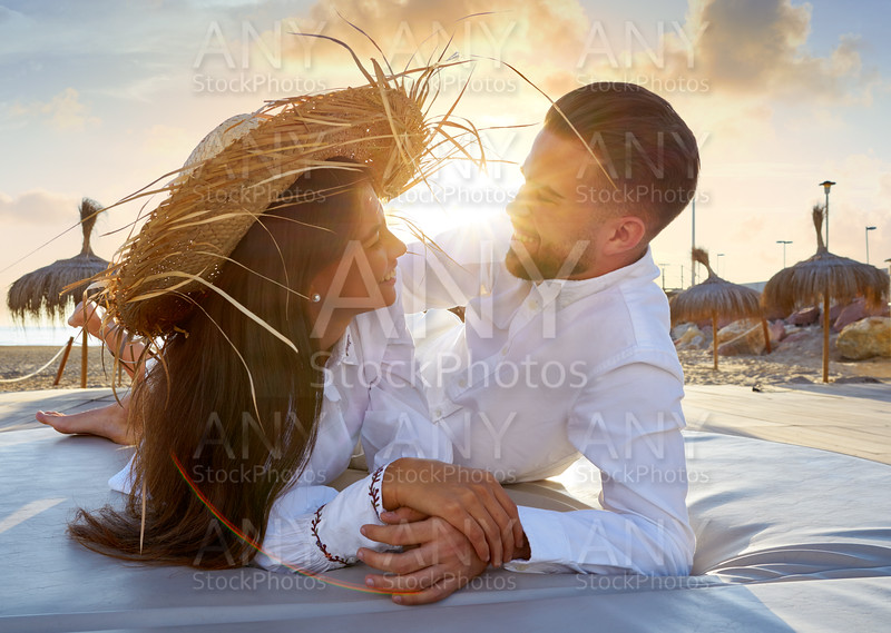 Couple young on beach lounge sunset