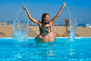 Tourist couple piggyback in infinity pool