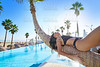woman lying on pool bent palm tree trunk