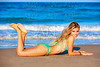 Blond bikini girl young lying on the beach sand