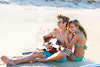 Blond couple sitting in a beach sand playing guitar